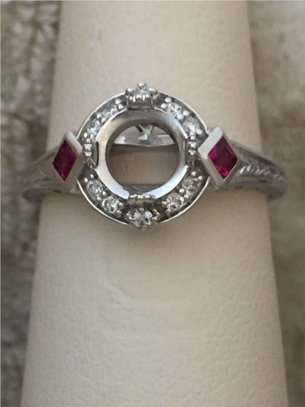 Ring - Round Halo Semi-Mount Diamond and Ruby Ring in 18kt White Gold with Engraved Design. (D 1/8 carat weight and R 1/8 gem weight, does NOT include center stone as shown)