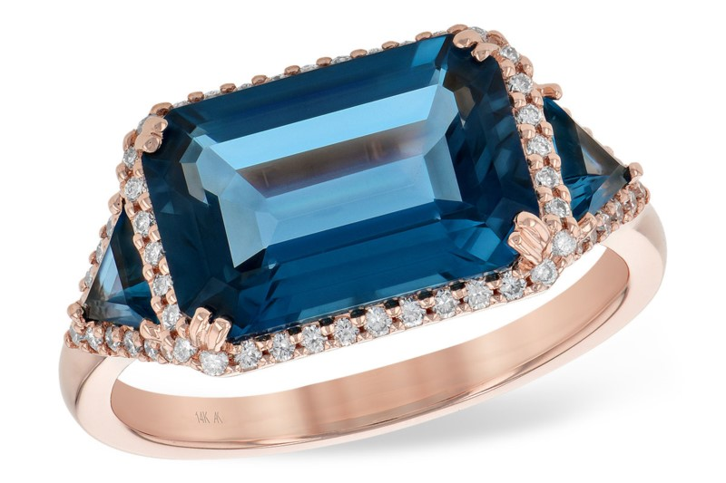 Emerald Cut Blue Topaz Ring - Made in 14 karat rose gold, this London Blue Topaz ring features a 4.60ct emerald cut center flanked by trillion cut London Blue Topaz stones, all surrounded by .22ct diamonds. This stunning and unique ring is available in size 7.