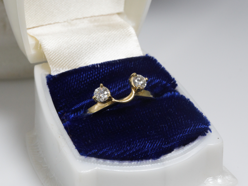 Gold wedding ring wrap with two diamonds sitting in ring box