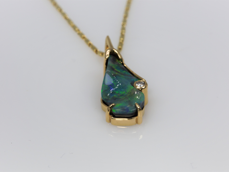 Black Opal Pendant - This beautiful black Opal stone has both a rugged yet polished finish with deep blues and green gleaming through. Both the Opal and small accent diamond on the left are set into 14kt yellow gold to make a stunning pendant. Custom designed and made in our Palm Harbor studio. Chain sold separately. This item is custom made to order. Please allow 5-8 weeks for shipping on custom designs. Stone size and shape can vary slightly on custom jewelry. Please call if you have any inquires about this pendant. 727-785-9624.