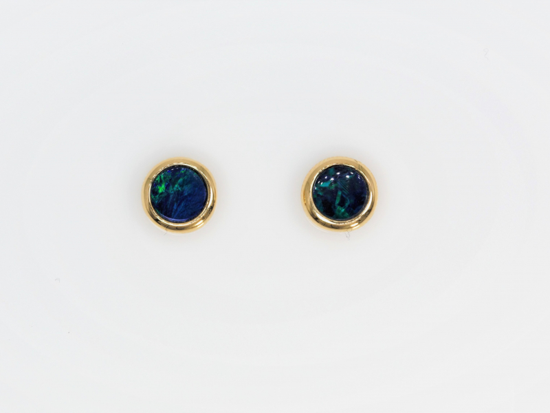 Opal Doublet Studs - These Opal Doublet stud earrings are bezel set into 14kt yellow gold. Deep blue color with green waves throughout, these earrings may be small but their intricate design makes them the perfect statement piece.