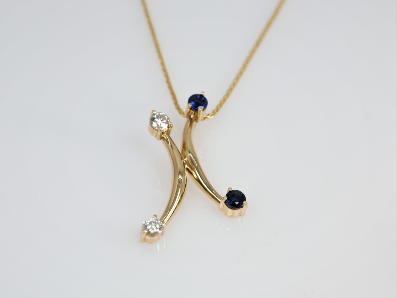 "Sapphire Jacks - This custom design is called ""sapphire jacks"". This pendant features 2 sapphires and 2 diamonds on each side of a yellow gold x shape pendant. This pendant is a custom design, made in our Palm Harbor studio. The total weight of this pendant is .32 and the total diamond weight is .22"