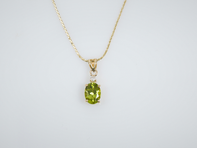Arizona Peridot Pendant With Accent Diamond - This peridot pendant features a juicy 1.30ct Arizona peridot and a .03ct accent diamond. Set into 14kt yellow gold. Chain sold separate.