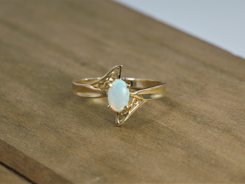 Opal Ring 14k Yellow Gold Filigree - 6.00x4.00mm white oval Opal set into a 14kt yellow gold band with a filigree triangle design on both sides.