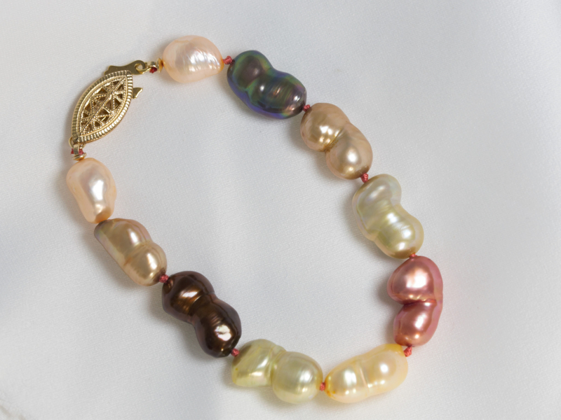 Multiple Colors Pearl Bracelet - Featuring 10 colorful freshwater pearls, this hand-strung pearl bracelet is a stunning statement piece. The iridescent pearls will glimmer off their fun colors. The pearl bracelet is strung with a fun pink string and held together by a gold filled pearl clasp.