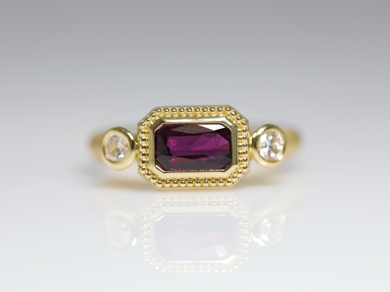 Etruscan Inspired Ruby and Diamond Ring - This stunning emerald-shaped red ruby ring is set in 18K royal yellow gold and is complimented with two diamonds. The Etruscan-inspired style ring features a 1.09 carat ruby that is sure to turn heads. This is a custom design from our Palm Harbor, Florida jewelry studio made by designer/jeweler Bob Shinsky. This would make a stunning fashion ring or alternative gemstone engagement ring!