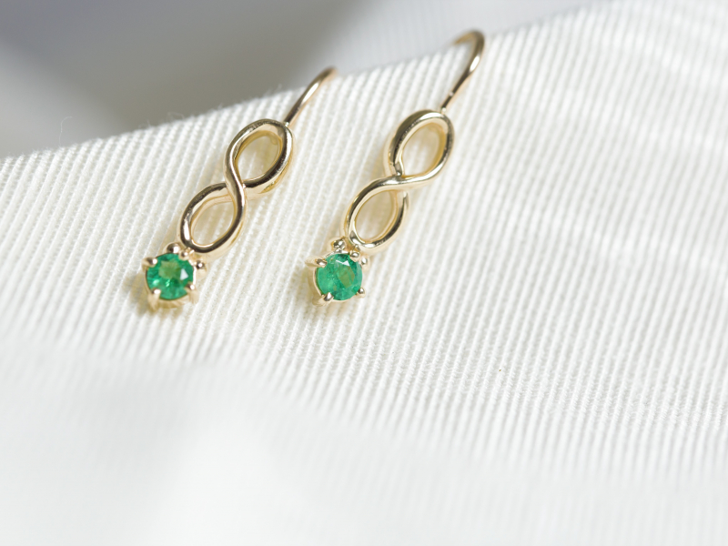 Emerald Infinity Drop Earrings - These custom earrings features 2 round .08 carat emeralds set into a 14k royal yellow gold infinity symbol. Custom made in our Palm Harbor, Florida jewelry studio and at a price that makes it gift worthy.