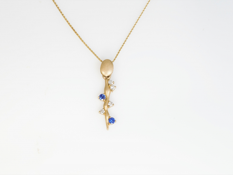 Sapphire Vine Pendant - This pendant features sapphire and diamonds set onto each side of a 14kt yellow gold twig like shape hanging down. This is a custom piece designed and made in our Palm Harbor studio. Chain sold separate.