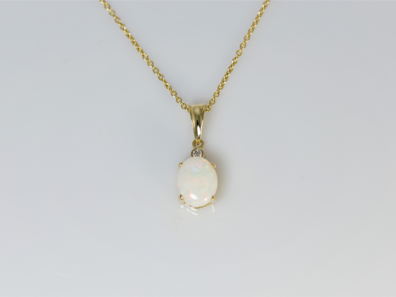 Opal Pendant - a 1.65 carat white opal set into 14k yellow gold with an accent diamond. This pendant is a signature design that's simple and versatile. Chain sold separate.