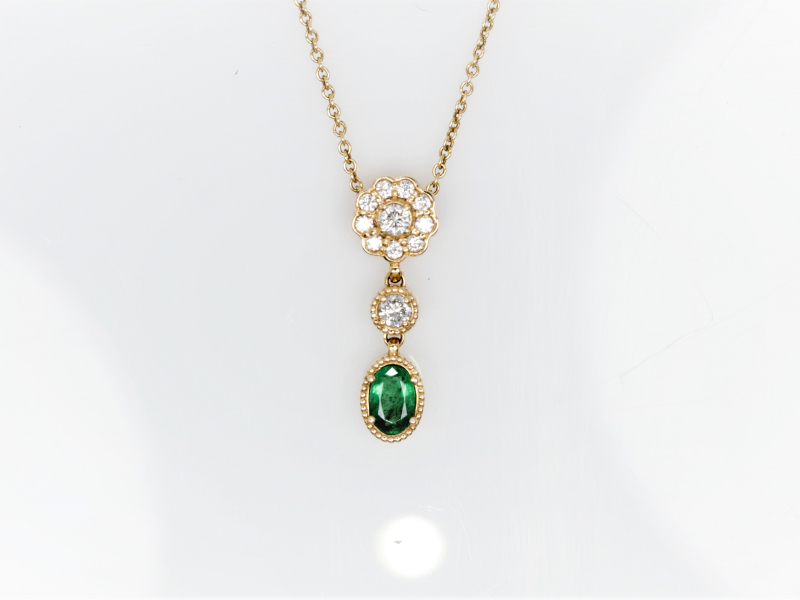 Emerald Pendant  - This 3 part pendant with a diamond flower, round diamond and emerald was custom made in our Palm Harbor studio. These gorgeous stones are set into 14 kt yellow gold and have a milgrain embellishment around them.