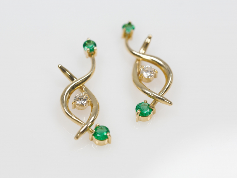 Emerald and Diamond Twist - This stunning pair of earrings features emeralds on each end of a double gold twist with a diamond accenting in the middle. Custom designed and made in our Palm Harbor studio. These earrings are made custom per order in numerous gemstones.